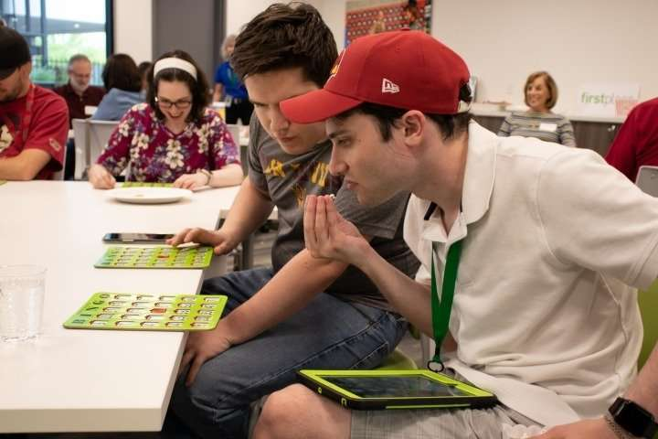 During a weekly game of bingo, one of Matt's favorite activities, a Transition Academy student and supportive neighbor keeps an eye on his friend's board to make sure Matt stays on track.