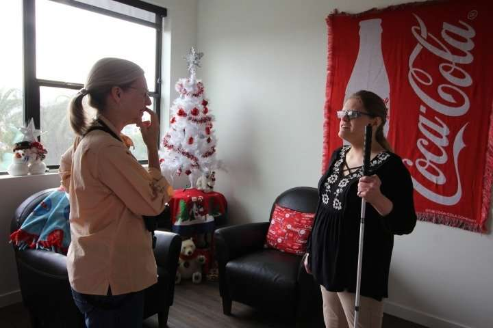 National Geographic photojournalist Lynn Johnson talks with First Place–Phoenix resident Lauren in her Coca Cola-themed apartment during a portrait session. Lynn develops a rapport with her subjects, making them more comfortable in their environment.